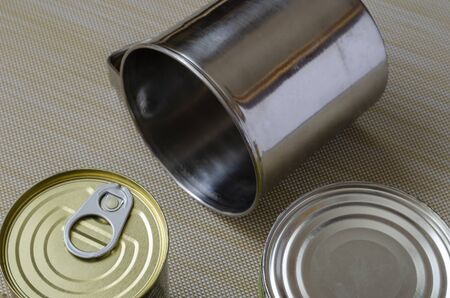 Two metal mugs and a can of canned food on a textured background. Stainless steel mugs next to canned food. Crockery and food for hiking, fishing, hunting. View from above. 版權商用圖片