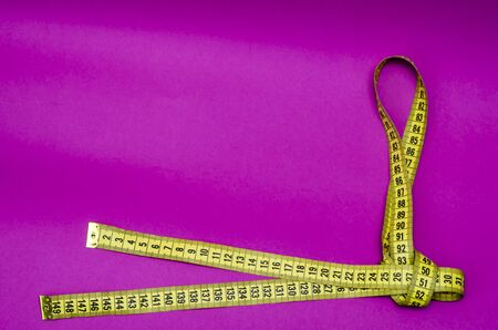 Yellow tailor measuring tape on a lilac background. Twisted measuring tape with decimal scale. Multitask background. Copy space. Selective focus.