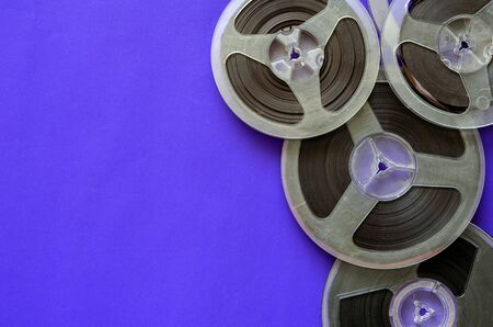 Magnetic tape reels on blue. Random bobbins with audio recordings. Nostalgia, pleasant memories. Copy space. Flat lay.