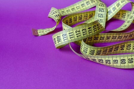 Yellow tailor measuring tape on a lilac background. Twisted measuring tape with decimal scale. Multitask background. Copy space. Selective focus. 版權商用圖片 - 148164551