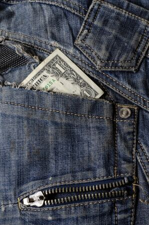 Dollar in the pocket of ripped jeans. One dollar bill in old jeans. The concept of crisis, poverty. Close-up. Copy space.