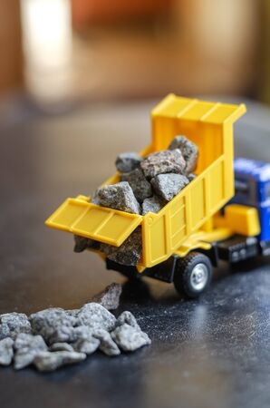 Plastic toy for children dump truck. The yellow dump truck pours gravel out of the body. Toys for kids. Educational games. Selective focus. Close-up.
