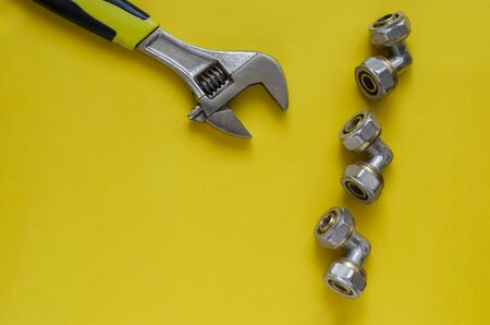 Creative background with hand tools and plumbing fittings on yellow. Adjustable wrench and three bronze corner fittings for multilayer water pipes. View from above.