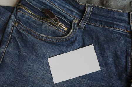 Blank white business card on top of blue jeans. Closeup of the front of a jeans with a blank form. Trade, business. View from above. Selective focus. Archivio Fotografico