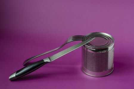 Fork, knife and can on a purple background. Open tin can and metal cutlery. Hiking, travel. Close-up. Copy space.
