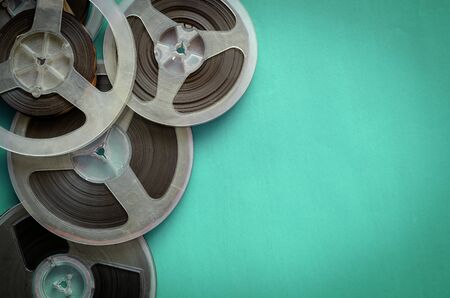 Reels with a magnetic tape on turquoise. Random bobbins with audio recordings. Nostalgia, pleasant memories. Copy space. Flat lay. Standard-Bild