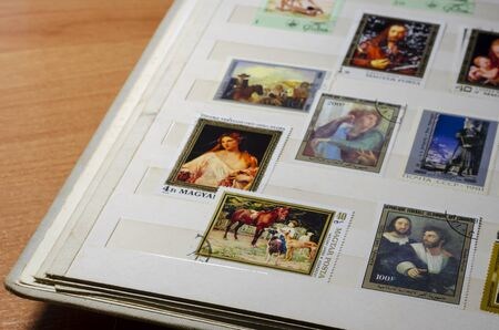 Thematic Collection of old postage stamps in the album. Pictures, painting, art. Collecting, philately. Selective focus.