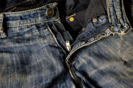 Grated jeans with a zip fastener and a button. Modern casual wear. Close-up. Front view.