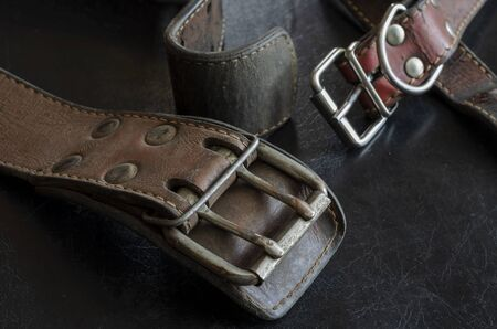 Fragment of two old genuine leather collars on a dark table. Cracked shabby leather and metal fittings. Real vintage dog collars. Love to the animals. Selective focus.