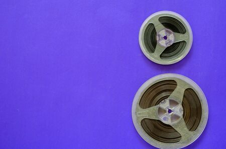 Reels with magnetic audio tape. Two plastic bobbins on a colored background. Creative minimalistic multitask background. View from above.