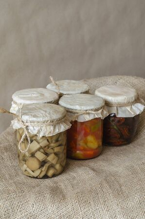 Canned mushrooms, lecho and other home-made canned food. Canned food in glass jars. Various canned food on burlap. Preservation and storage of crops. Close-up. 스톡 콘텐츠