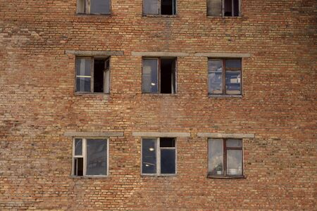 Old brick dormitory building of the times of the USSR. Soviet architecture. A collapsing brick wall with broken and open windows. Real residential building.