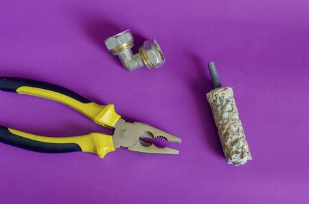 Pliers, boiler anode and bronze fisting on a purple background. Warranty and after-sales service of water heaters. Copy space.