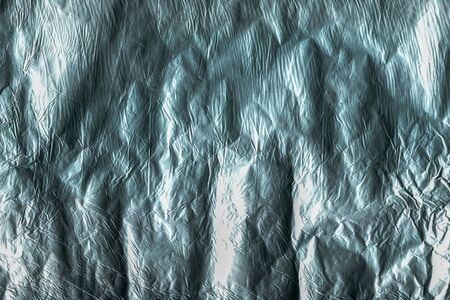 Turquoise aluminum foil texture. Crumpled aluminum foil with shadows and highlights. Multitask background for various design tasks. View from above.