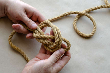 Hands of an adult man knit knots from hemp rope. Man of Caucasian ethnicity, age 44-45 years. Top view at an angle. Selective focus. Reklamní fotografie
