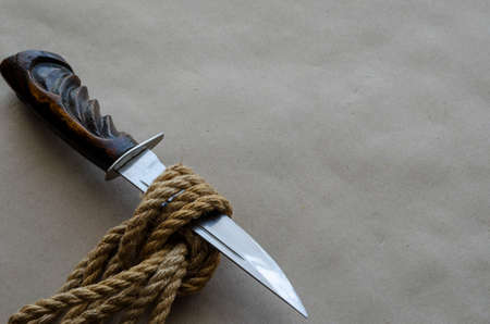Large knife with a wooden handle is stuck in a hemp rope knot. Decisive and cardinal problem solving. Metaphorical background. Top view at an angle. Selective focus. Stok Fotoğraf