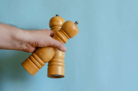 Adult man holds in his hand two wooden pepper mills. Devices for grinding spices from hard wood. Male of European race, 43-45 years old. Kitchen utensils
