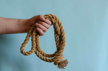 Hemp rope scroll with a knot in a male hand. The hand holds a thick natural cable. Adult male of European race. Marine subjects. Sports and recreation.