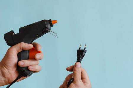 Glue thermo gun in a male hand. An electric device for gluing objects with sticks of glue. Middle-aged man of European race. Hand-held power tools for work and creativity Stok Fotoğraf