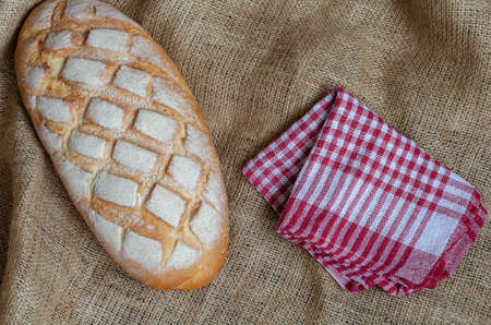 Flat lay loaf of bread and red checkered napkin on burlap. Baking homemade craft bread. Small family business. Baker's craft.