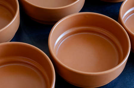 Empty clay bowls. A group of brown soup bowls on the table. Catering. Selective focus. Reklamní fotografie