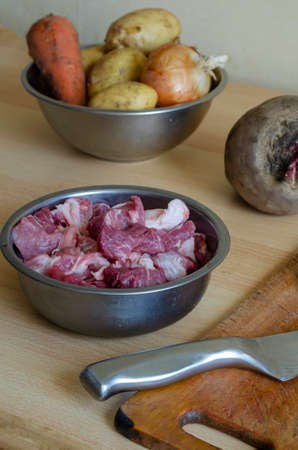 Metal kitchen knife, raw vegetables, cutting board and bowl of raw meat pieces. Pork shoulder, cut into pieces and unpeeled vegetables. Home cooking. Selective focus.
