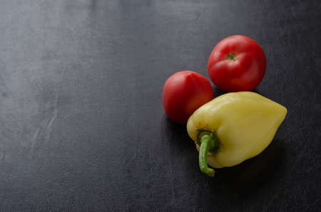 Sweet peppers and two ripe red tomatoes on a black table. Fresh organic vegetables. Farm products. Agroindustry. Foto de archivo