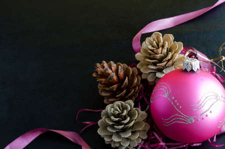 Christmas festive background. Three pine cones and a pink glass Christmas ball on a black background.