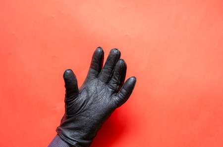 Male hand in a leather glove on coral background. The man is showing his hand in a black leather glove. Side view. Selective focus.
