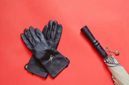 Female leather gloves and an umbrella on coral background. Pair of black gloves next to an elegant umbrella. Top view at an angle. Copy space