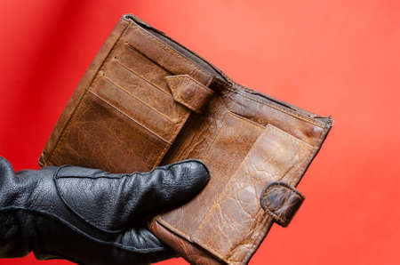 Hand in black leather glove holds out empty brown wallet. Male hand holds stolen wallet with no money. Theft concept. Side view. Selective focus.