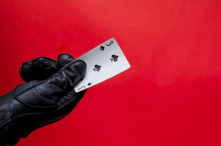 Male hand in leather glove holds playing card. The right hand in black glove with triplet of clubs on corral background. Fortune telling or magician concept. Side view. Selective focus.