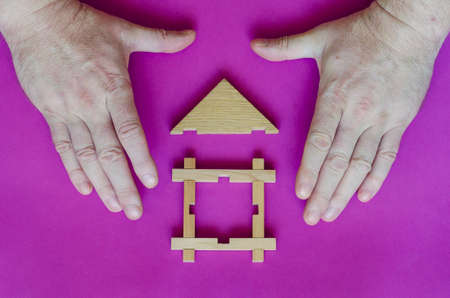 Hands are protecting a small toy wooden house. The hands of an adult man protect a wooden house on a purple background. Real estate insurance. Private property protection.