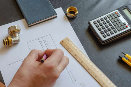 A male hand draws a diagram of home plumbing. Plumber makes the calculations. Caucasian man of middle age. Plumbing services.