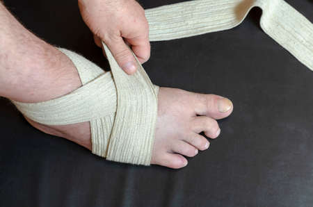 Middle-aged Caucasian man produces an independent bandage of his dislocated leg. He puts an elastic bandage over his swollen shin. First aid in sprains and dislocations. Bandage stabilizes ankle joint. Stock fotó