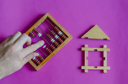Male hand calculates an abacus next to toy wooden house on lilac background. The concept of mortgage or lending secured by real estate. View from above. Stockfoto