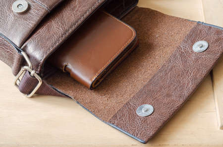 Brown leather wallet inside small shoulder bag. An open bag and brown leather wallet on wooden background. Top view at an angle. Selective focus. Stock fotó