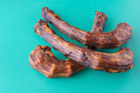 Three Dried turkey neck on a turquoise background. Dental treats for pets. Natural treats for promotion and pampering. Pet supplies. Banque d'images