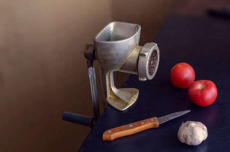 Manual vintage meat grinder, knife and vegetables on the table. Ripe tomatoes and a head of garlic. Use of outdated kitchen utensils.