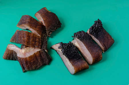 Pieces of raw cow stomach on turquoise. Random pieces Black unpeeled tripe with grass residues. Beef offal. Close-up. Imagens