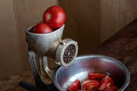 Manual vintage meat grinder and ripe tomatoes on the table. Making homemade tomato sauce. Use of outdated kitchen utensils.