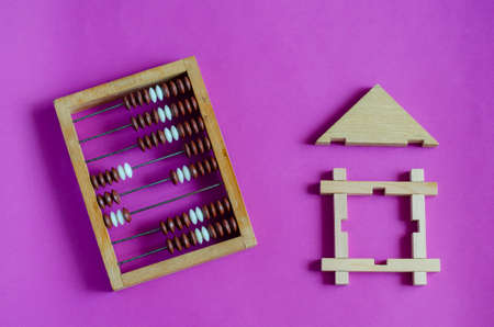 Wooden toy house and wooden abacus on a lilac background. The concept of mortgage or lending secured by real estate. View from above. Copy space.