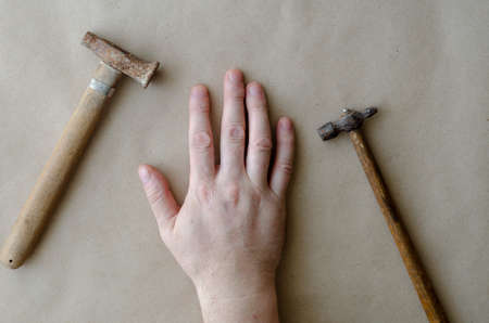 Caucasian man bowed his hand next to the small hammers. The hand of a middle-aged man and two old hammers. Manual labor. Selective focus.