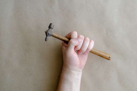 Caucasian man holds a small hammer in his hand. Hand of a middle-aged man with a hand tool. Manual labor. Selective focus.