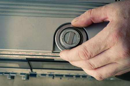 Adult Caucasian male hand tunes radio on retro stereo cassette recorder. Vintage audio equipment of the last century. Selective focus.