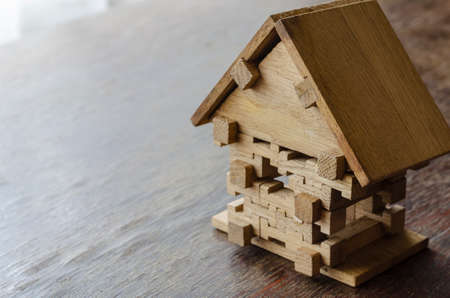 Wooden toy house on a wooden table. Small house made of oak puzzles. Side view at an angle. Selective focus. Copy space