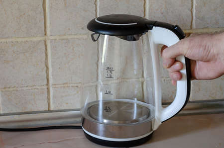 Male hand puts an empty electric kettle on the kitchen table. Glass teapot with freshly poured out water from it. Modern electrical appliances. Selective focus.