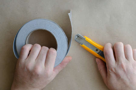 Hands of middle-aged Caucasian man are working with foil tape and knife. Heat and moisture insulation services. Modern insulating materials. Selective focus.