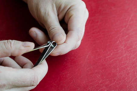 Middle-aged Caucasian man cuts his own nails. Nail clippers in male hands on a red table. Health and hygiene. Close-up. Imagens