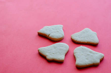 Homemade Christmas cookies on red background. Traditional holiday baked goods. Copy space. Side view. Selective focus